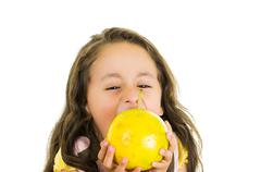 Adorable healthy little girl eating a passionfruit in front of her face Stock Photos