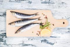 Fresh anchovy fish on wooden kitchen board. - stock photo
