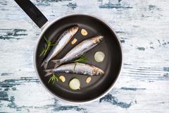 Raw fish on pan - stock photo