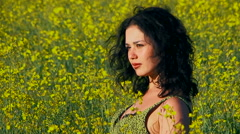 Curly woman is sitting in a field of Raps Stock Footage