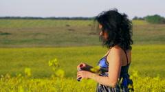 Happy woman is blowing bubbles in a field of Raps Stock Footage