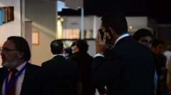 Executive talking on mobile phone in trade fair. - stock footage