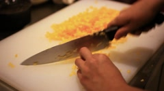 Cook is chopping bell pepper, closeup. Chef finely cutting vegetables on plank Stock Footage