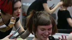 young female model smiling wen being applied make up and hairstyle - stock footage
