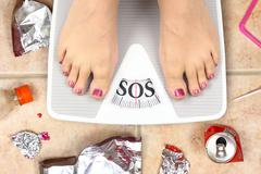 Feet on bathroom scale with word SOS and junk food garbage Stock Photos