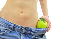 Woman's fit belly with green apple and oversized jeans, isolated on white. - stock photo