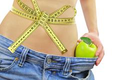 Woman's fit belly with measuring tape,apple and oversized jeans, isolated on  - stock photo