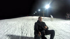 4K Happy man on sled having fun on ski slope at night lit by reflectors. UHD Stock Footage