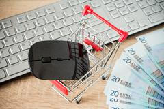 Shopping cart with mouse in front of computer keyboard - stock photo