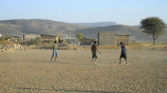 Children play football on a dirt pitch in Abala in Ehtiopia - stock footage