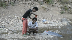 Hairdresser working on the bank of the river, Abala, Ethiopia Stock Footage