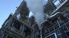 Low angle shot of smoke from a petroleum refinery Stock Footage
