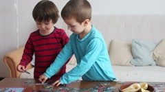 Smart little boys, brothers, making puzzle at home during a weekend day Stock Footage