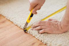 close up of male hands cutting carpet - stock photo