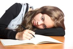 The girl-teenager looks in  writing-book Stock Photos