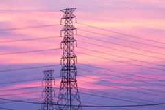 Silhouette electric pylon shot against sunset background Stock Photos