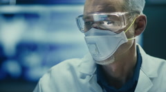Stock Video Footage of Portrait of Scientist in Safety Glasses and Respirator. Looking into Camera