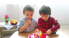 Adorable cute kids, blowing candles on a birthday cake at home Arkistovideo