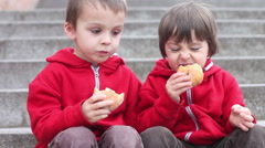 Cute kids, eating donuts outdoor in the afternoon Stock Footage