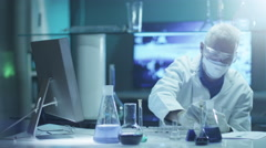 Scientist does Chemical Experiment in Laboratory - stock footage