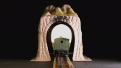 Model train driving through a tunnel into focus Stock Footage