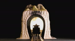 Model train driving through a tunnel into focus - stock footage