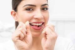 Woman cleaning teeth with floss - stock photo