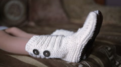 Legs of woman in white knit socks are moving to the music Stock Footage