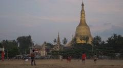 Boys play soccer in front of Shwemawdaw Paya,Bago,Burma Stock Footage