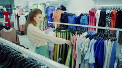 Young girl in shop buying clothes Stock Footage