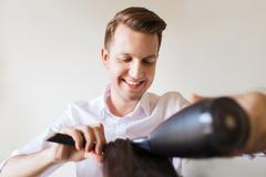 happy stylist with fan making blow-dry at salon - stock photo