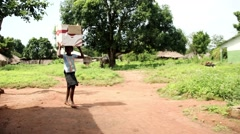 Young girl with papper box Africa village Stock Footage