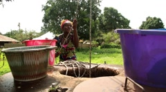 Girl takes water from  well Stock Footage