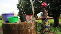 girl takes water from  well - stock footage