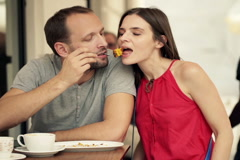 Couple talking and sharing food in cafe in the city NTSC Stock Footage