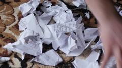 Hand pick torn and crushed documents from floor - stock footage