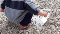 Baby plays with puddle zoom out 2 - stock footage