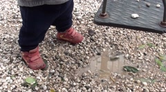 Baby in front of puddle Stock Footage