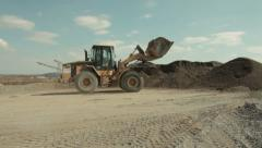Bulldozer pouring sand on pile, pan right on conveyor with sand, sand separation Stock Footage