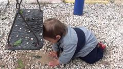 Baby plays with stones in puddle Stock Footage