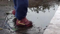 Baby steps into puddle 2 Stock Footage