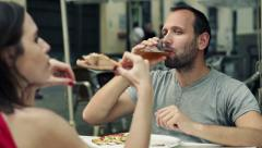 Couple talking, eating pizza and drinking beer in cafe in the city HD Stock Footage