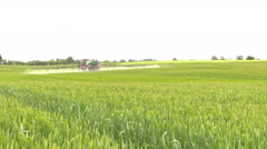 Farm tractor spray summer season green crop field Stock Footage
