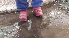 Funny toddler in puddle Stock Footage