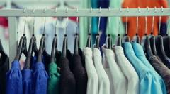 DOLLY MOTION: Variety of clothes hanging on rack in boutique Stock Footage