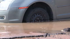 Sinkhole and water main break with flooding and car in sink hole Stock Footage