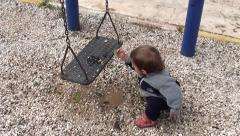 Toddler plays with stones from puddle 2 Stock Footage