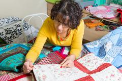 dressmaker working on her patchwork - stock photo