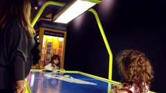 Closeup two young grils playing air hockey table game Stock Footage