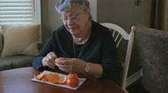Mature Woman Peeling Orange Stock Footage